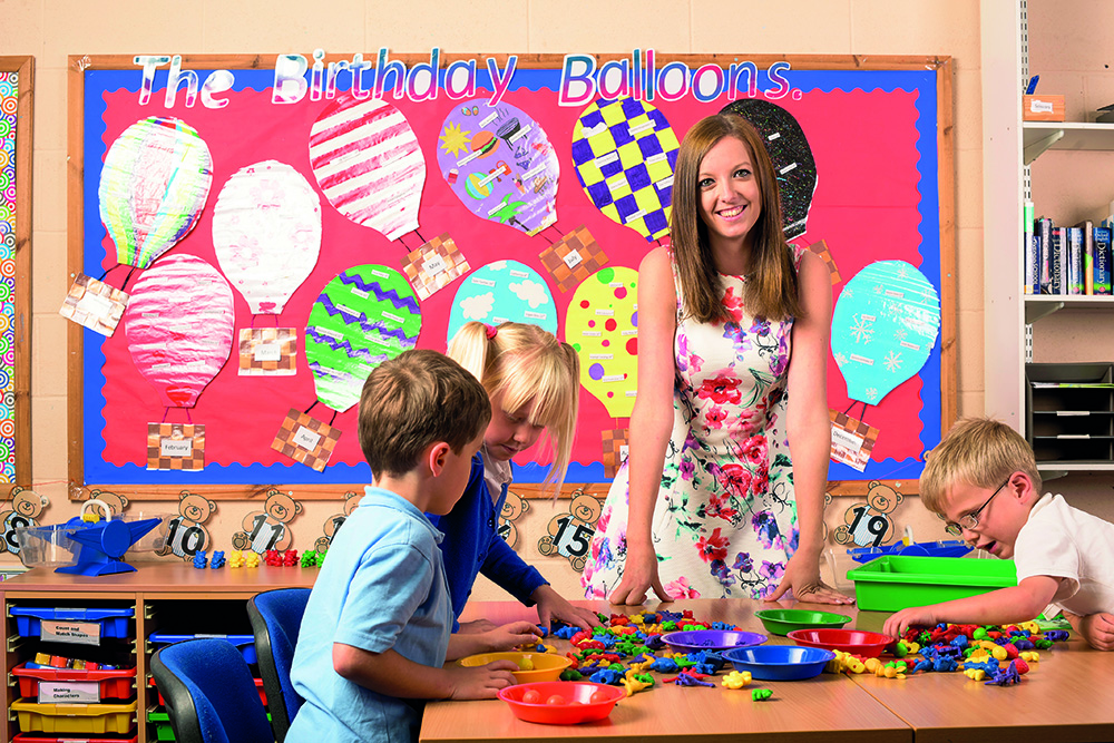 Image of a female teacher with three students about 6 years old, in a classroom