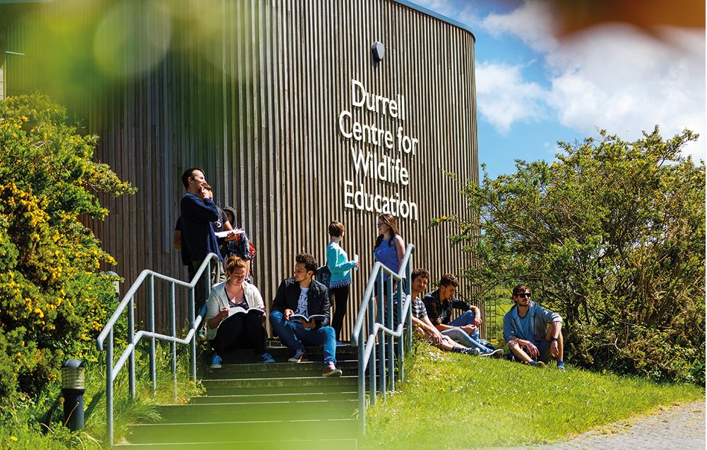The building Durrell Centre for Wildlife Education at Cornwall College Newquay. It is a sunny day and ten students sit or stand on the steps and grass outside the building