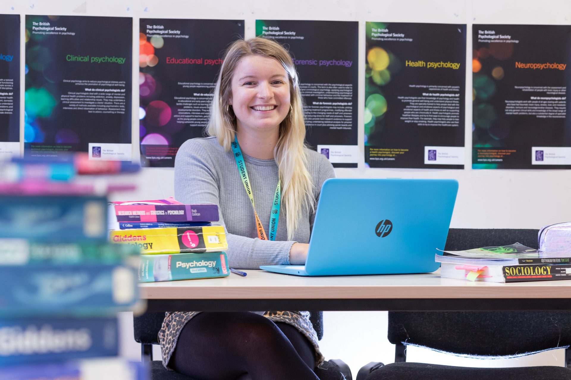 Woman sitting at desk with laptop and biology text books