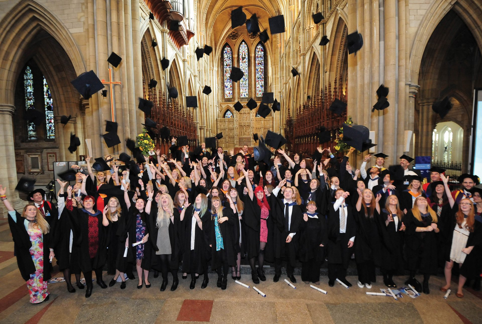 Students graduating at Truro cathedral throwing mortar boards in the air