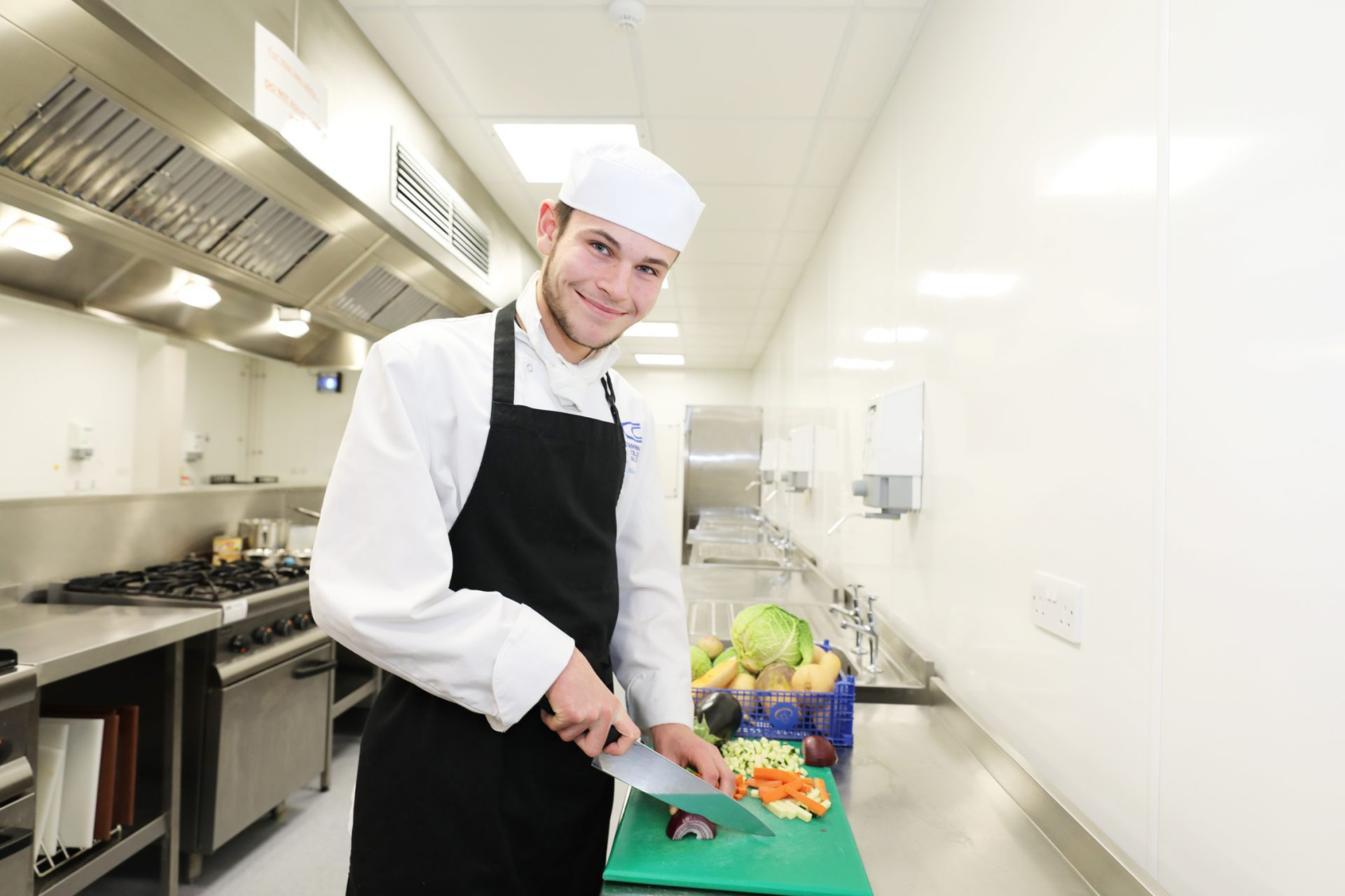 Student chopping onion in training kitchen at Cornwall College