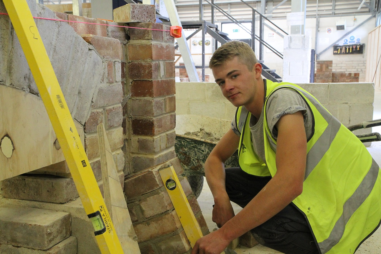 Cornwall College bricklaying student using a spirit level to check his work