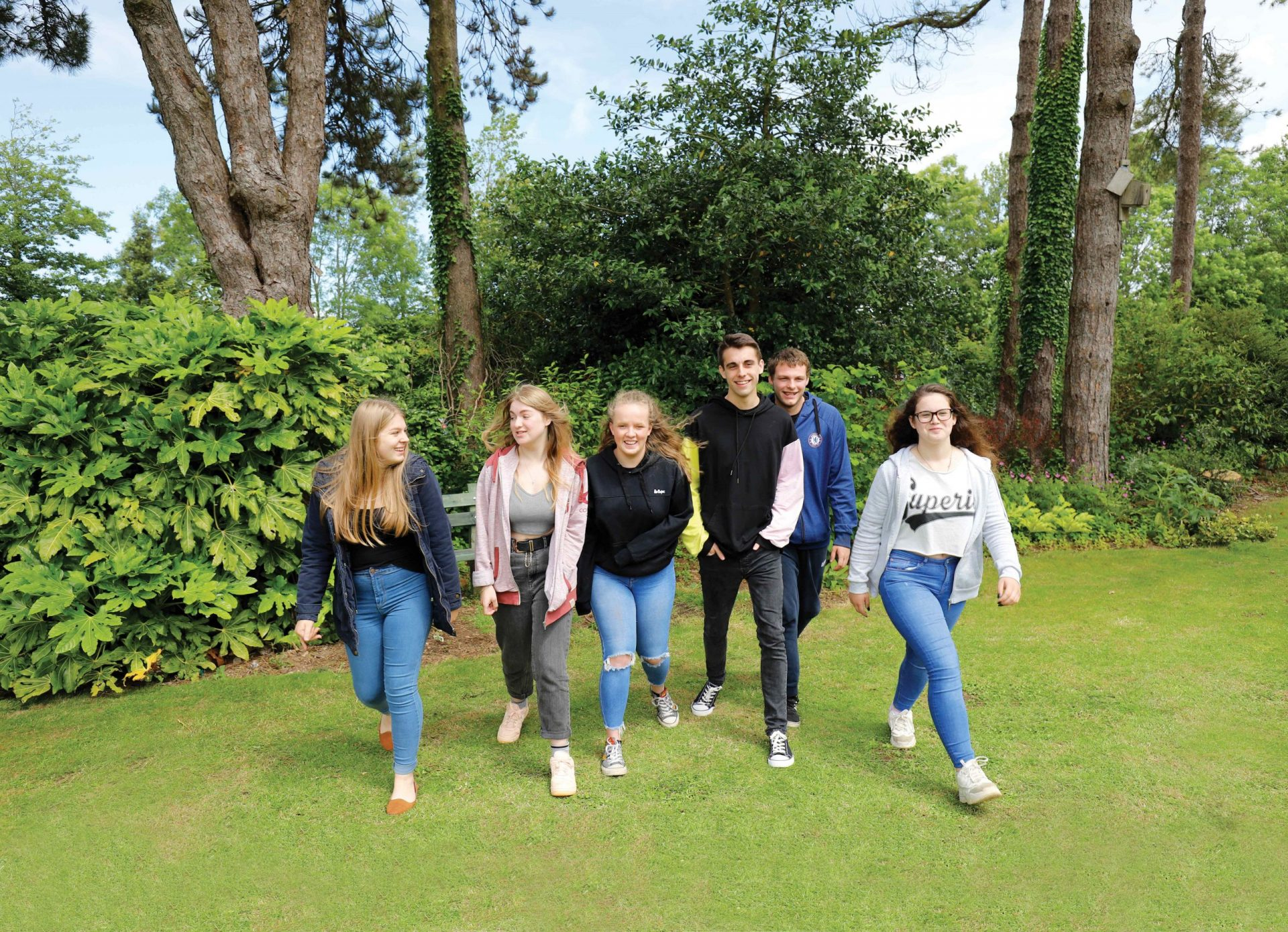 Group of students walking through garden smiling