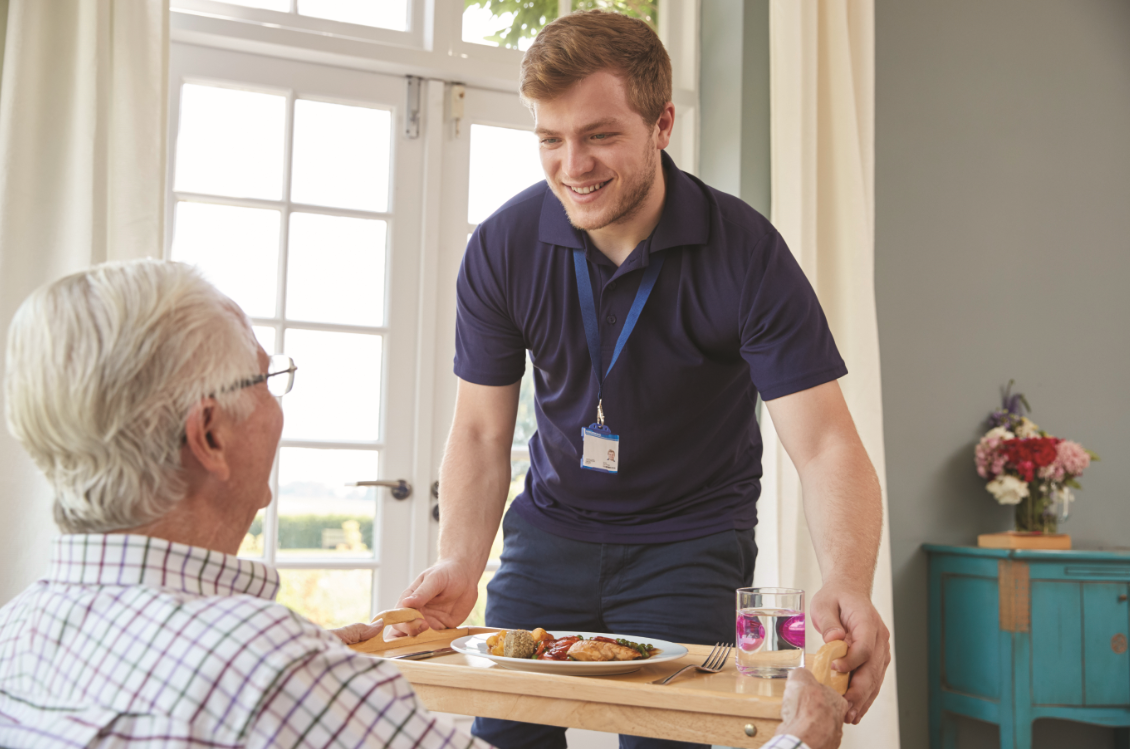 Male care worker serving food to an older adult