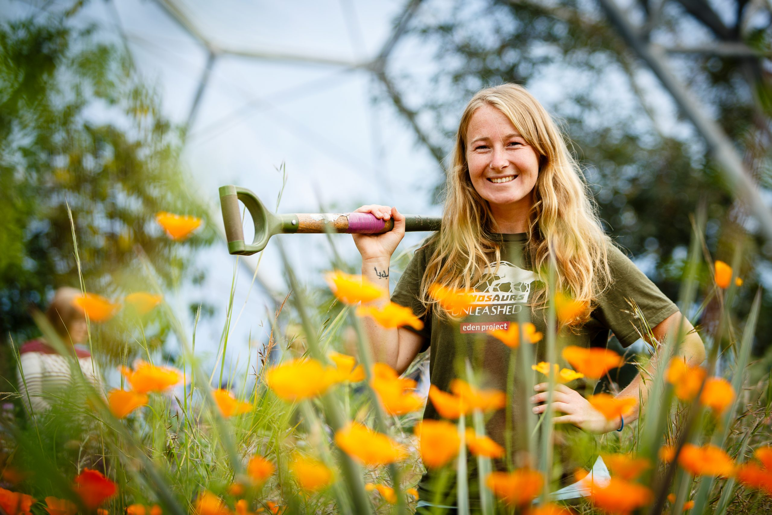 Female student posing behind orange flowers in a biome at Eden Project